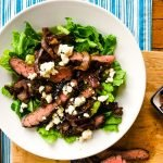 balsamic herb skirt steak salad over romaine lettuce with roasted red onions and crumbled blue cheese