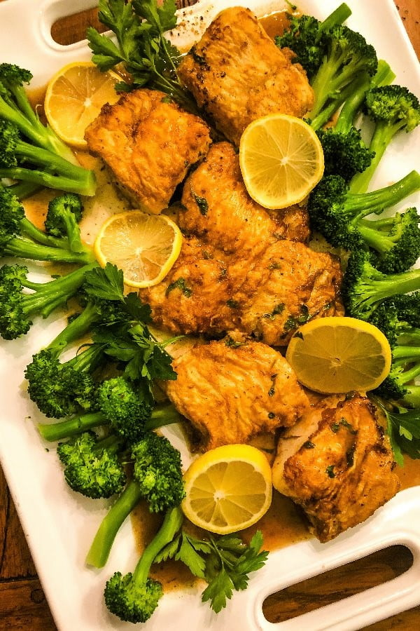 platter of fish cooked francese with lemons and broccoli