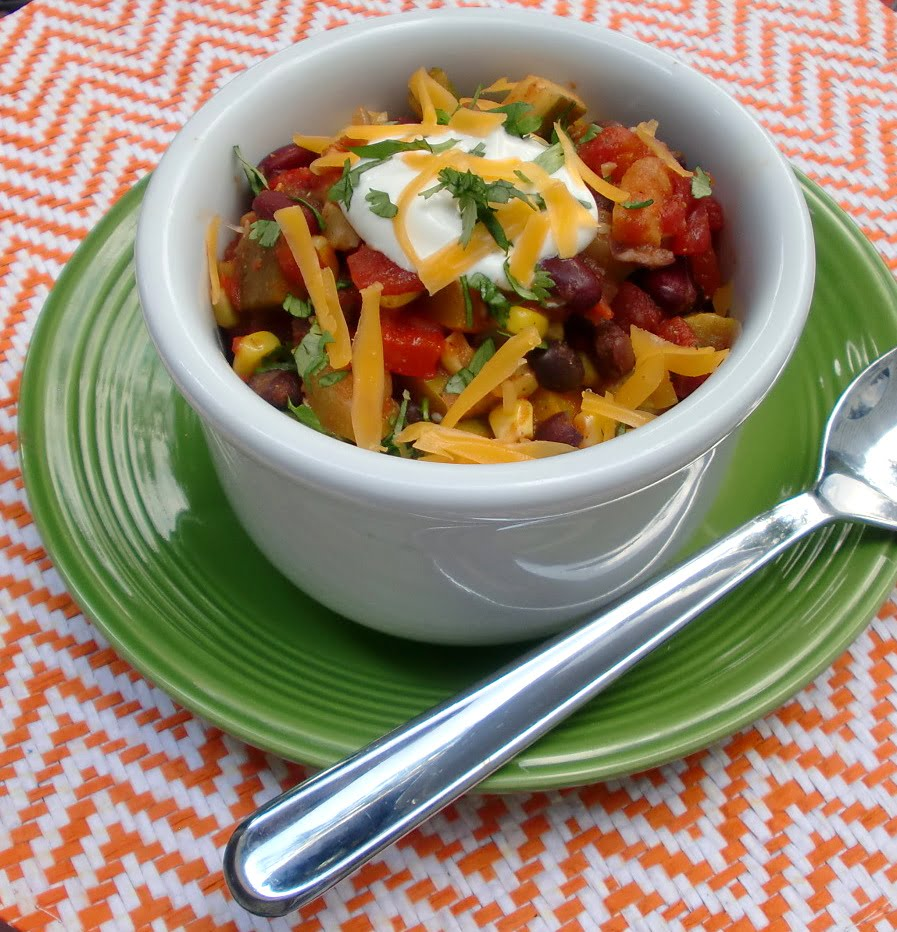 bowl of vegetable and bean chili topped with shredded cheddar cheese and sour cream