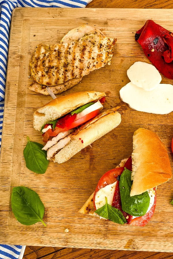 chicken mozzarella sandwiches and the ingredients on a cutting board