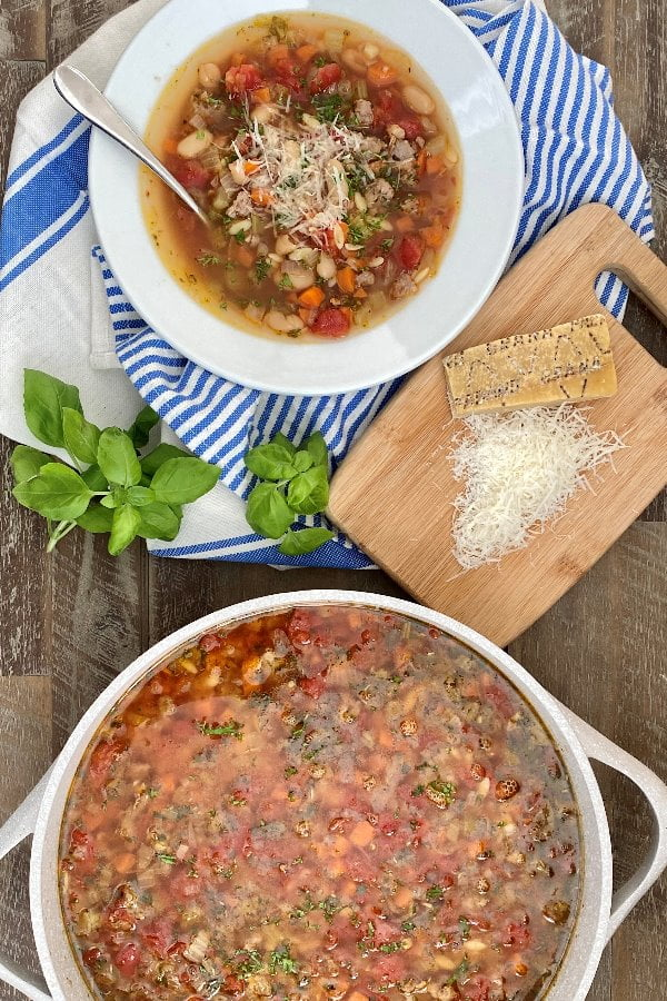 bowl and pot of pasta soup with Italian sausage and vegetables