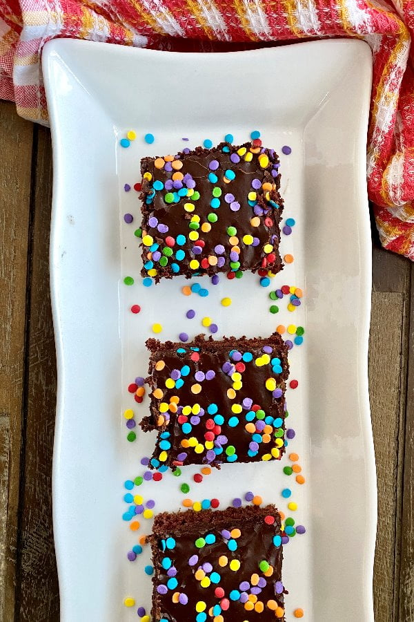 slices of chocolate texas sheet cake with rainbow sprinkles