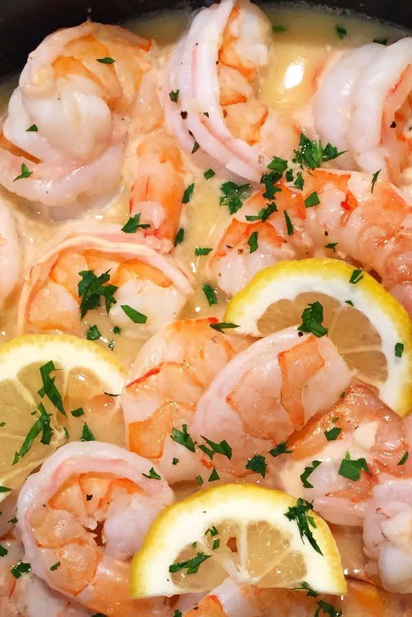 close up of garlic butter shrimp scampi with lemons