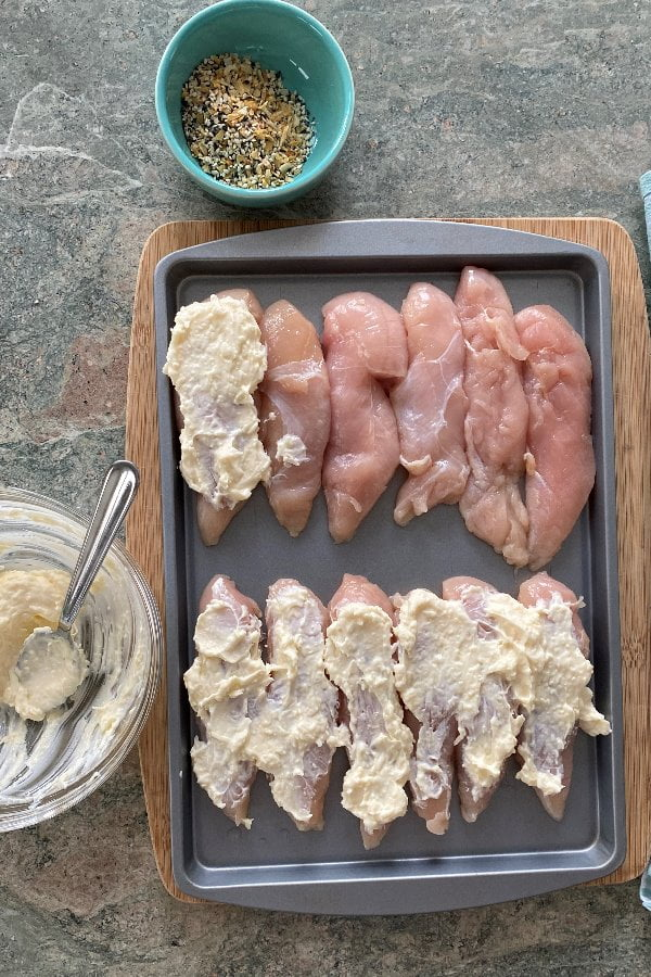 spreading chicken with parmesan cheese and mayo mixture