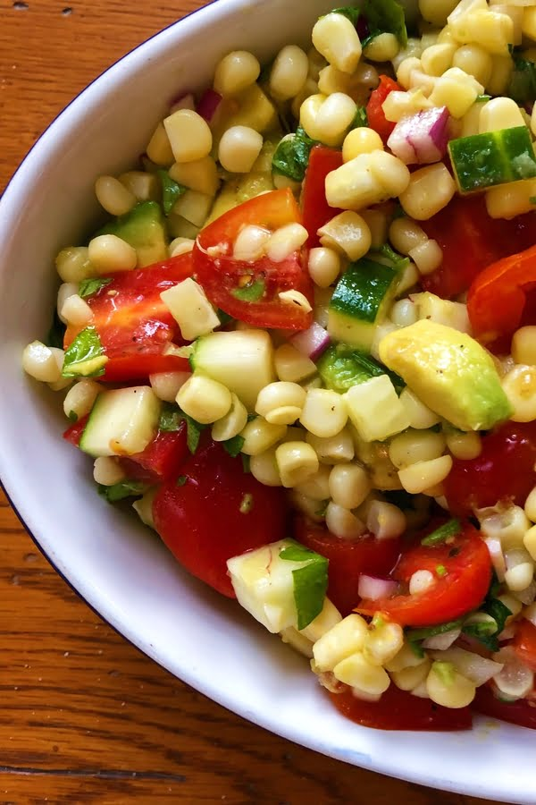 summery salad with corn, avocado, tomatoes and cucumbers