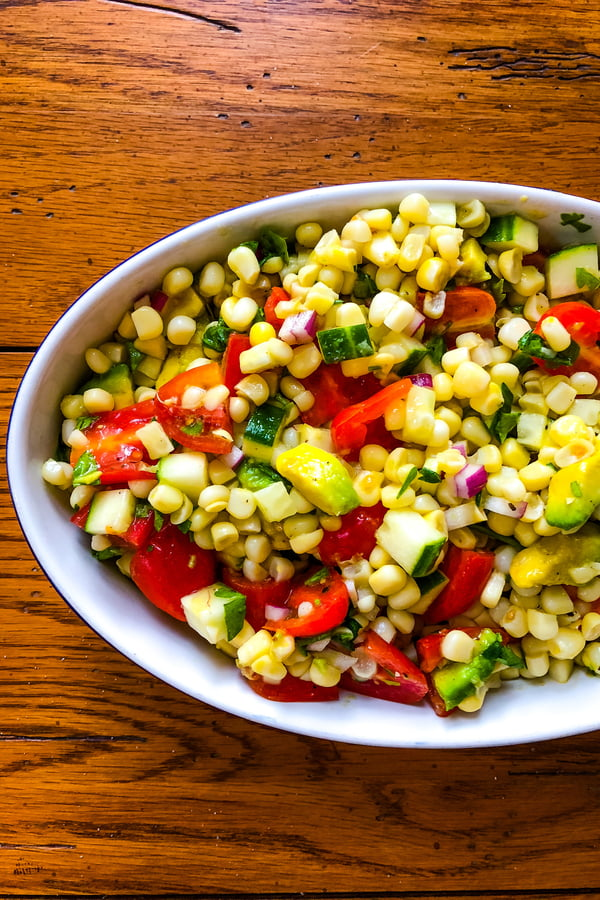 a side dish of summer produce with tomatoes and cucumbers