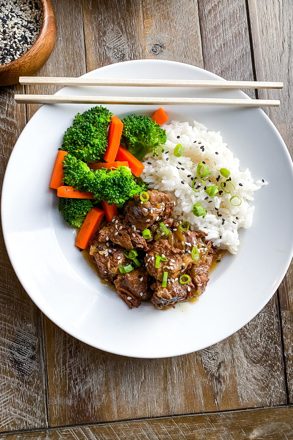bowl of Asian beef stew with rice, broccoli and carrots
