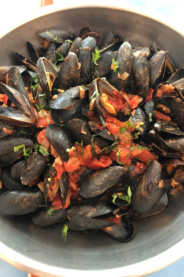 large bowl of mussels in a light marinara sauce