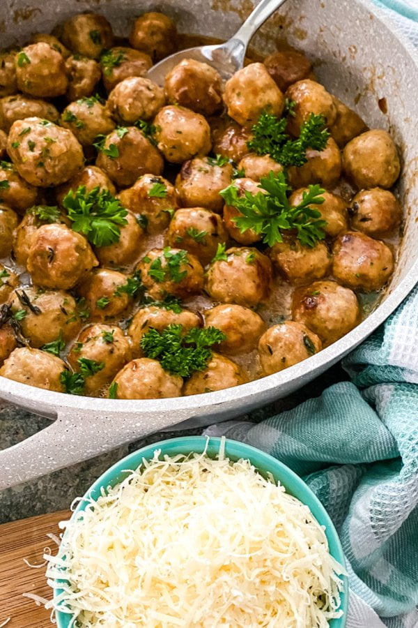 pan of cooked round balls of meat with Parmesan cheese