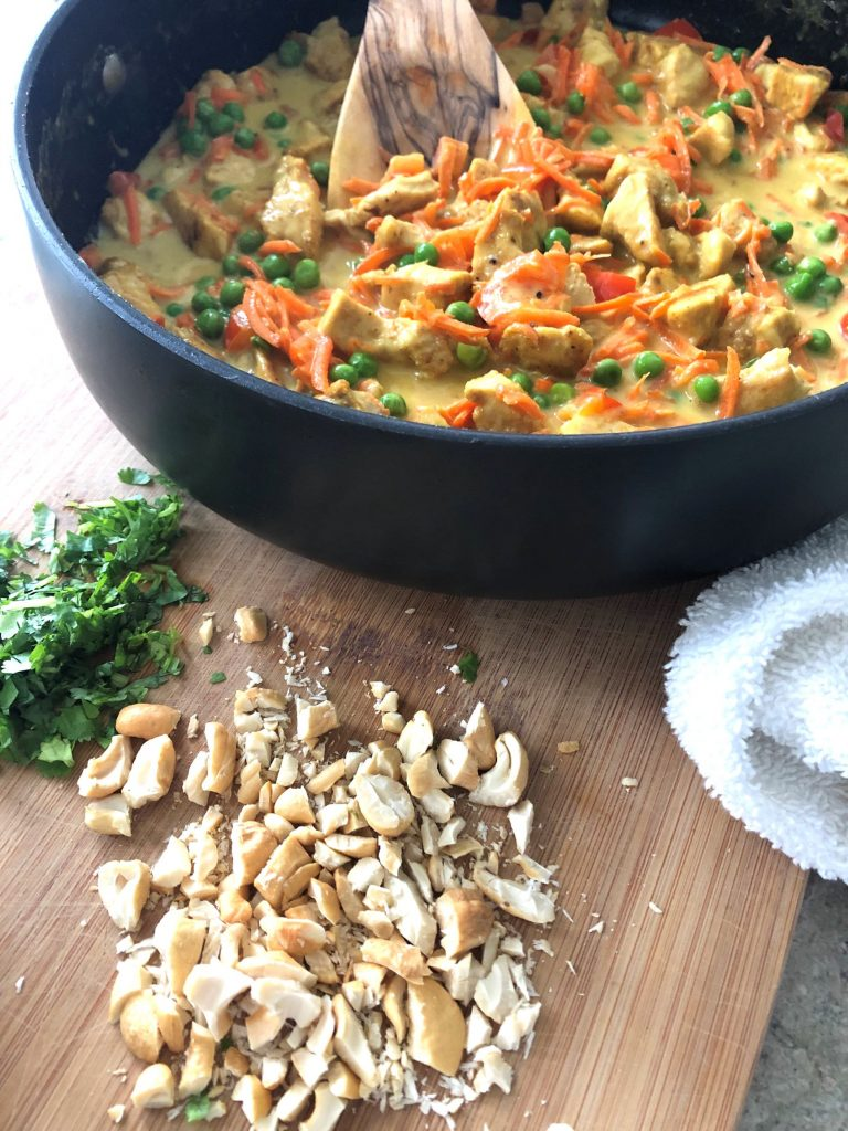 pan of Thai curry chicken with chopped cilantro and cashews