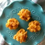 4 mac and cheese bites on teal colored plate