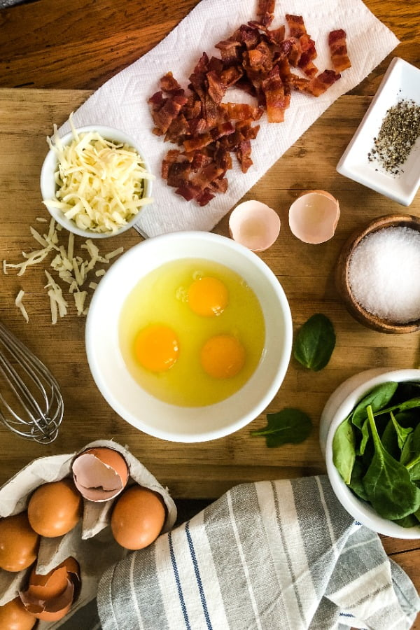 quiche ingredients - eggs, bacon, shredded cheese, spinach
