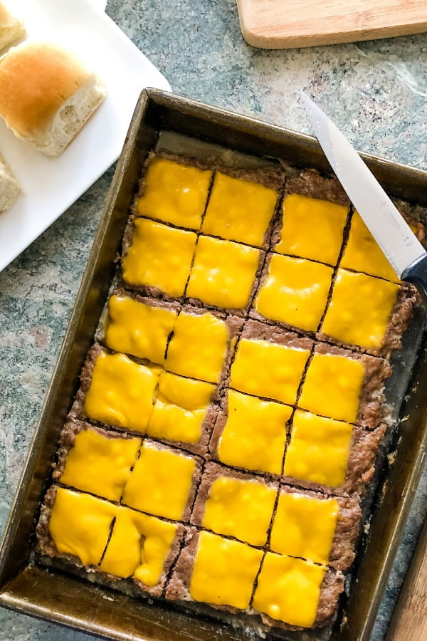 cheeseburger sliders recipe tops a large patty with melted cheese before cutting into small burgers