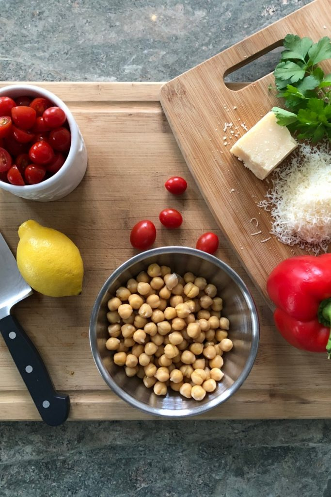 chickpeas, red pepper, lemon, cherry tomatoes, parsley and Parmesan cheese on a cutting board