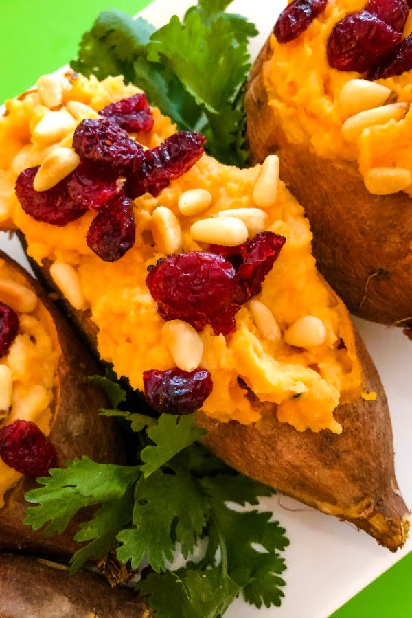 close up of a sweet potato topped with dried cranberries and pine nuts