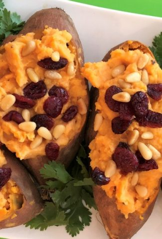 platter of coconut stuffed sweet potatoes topped with dried cranberries and pine nuts