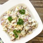 bowl of creamy potato salad with dill pickles