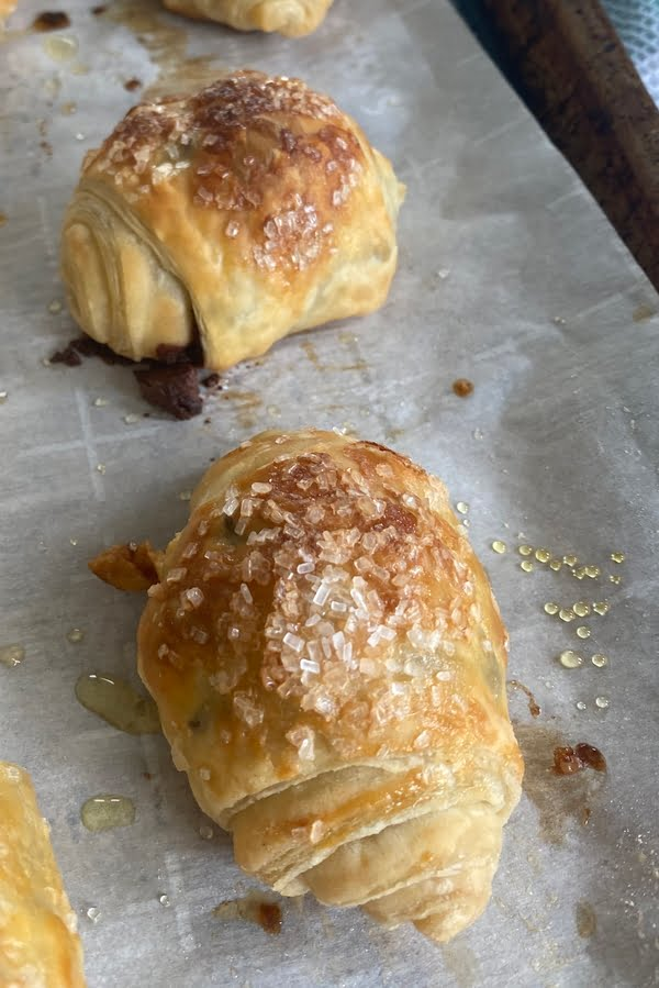 close up of 2 puff pastry rolls filled with chocolate