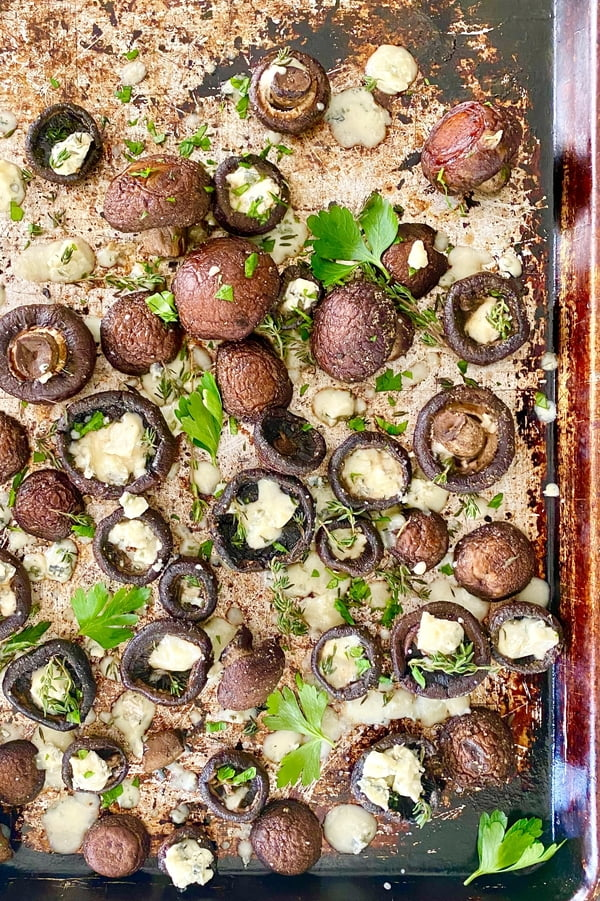 large baking sheet with baked garlic butter mushrooms, blue cheese and fresh herbs