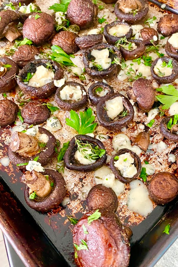 baked mushrooms with herbs on a baking sheet