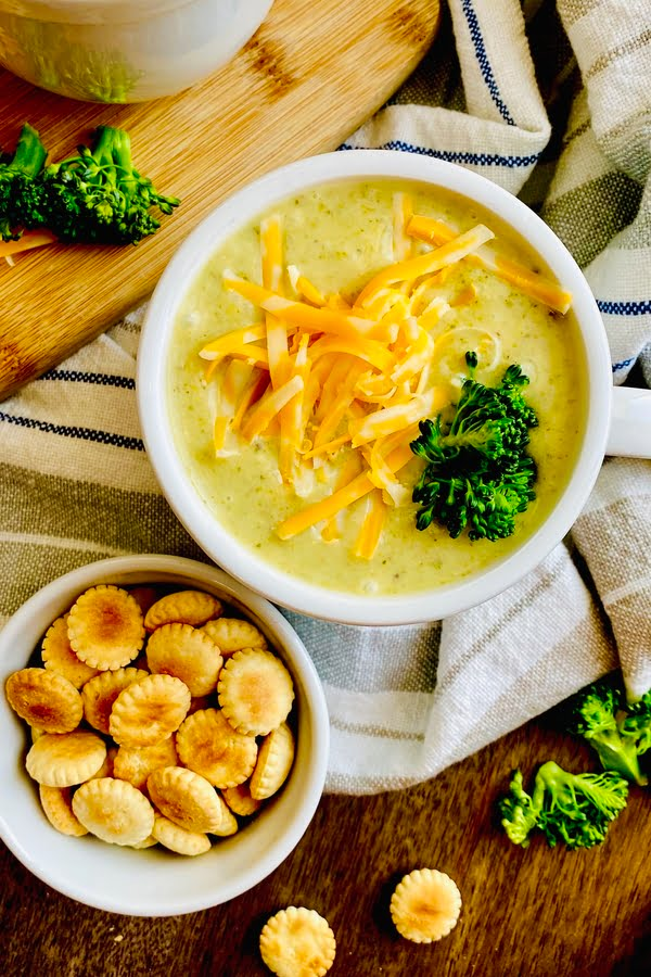cup of broccoli and cheese soup with oyster crackers