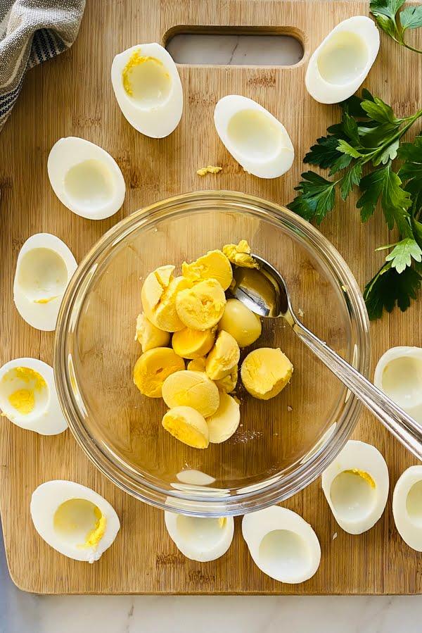egg white halves and hard boiled yolks in a bowl