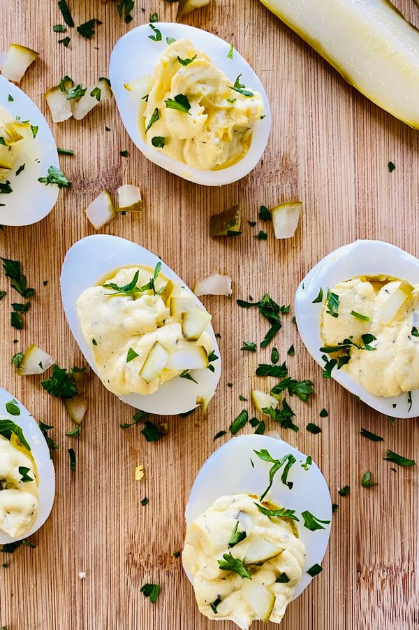 creamy deviled eggs with dill pickles on a cutting board