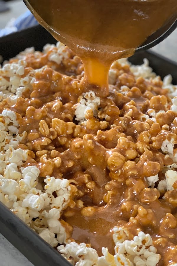 pouring sugary golden sauce over popped corn