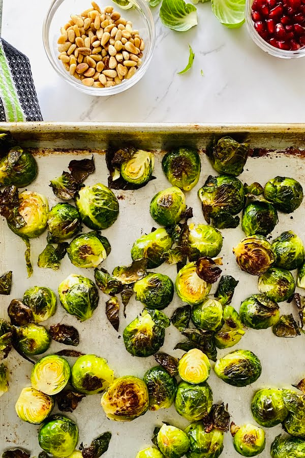 roasted Brussels sprouts on a baking sheet with honey