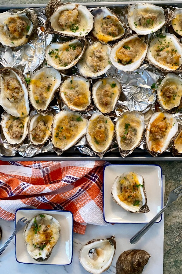 baking sheet with baked oysters with cheese