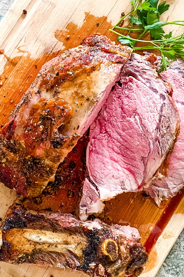 sliced slow roasted prime rib on a cutting board