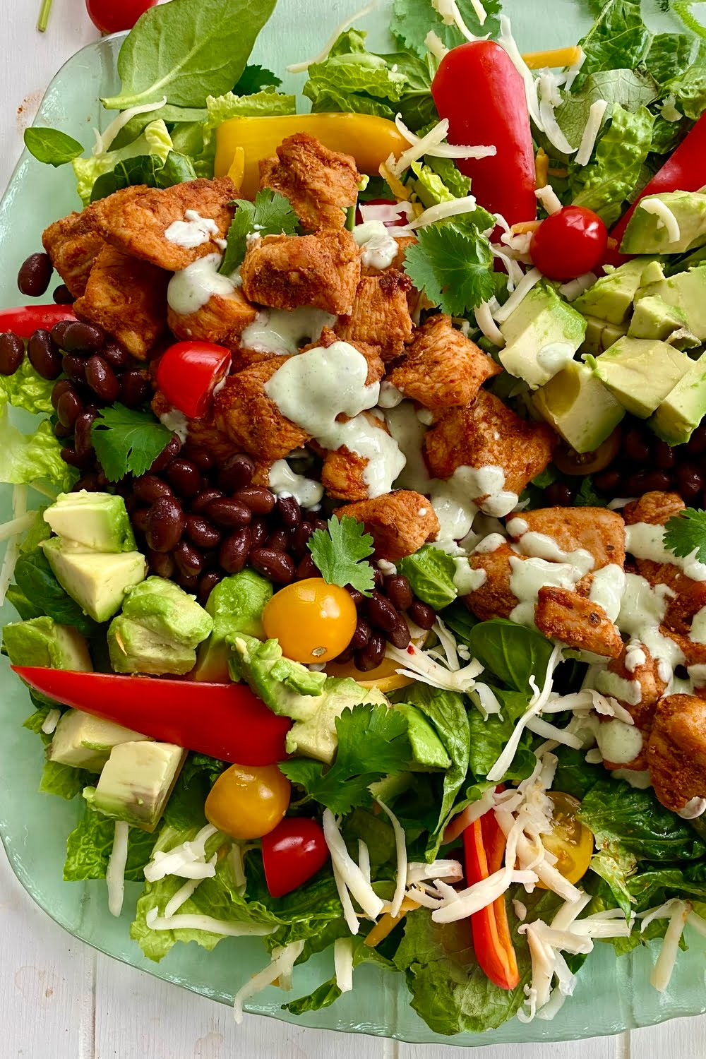a delicious southwest salad with chicken, avocado, pepper jack cheese and black beans